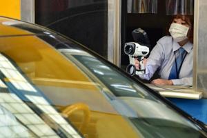 С помощью специальных приборов медики измеряют температуру людей в автомобилях
